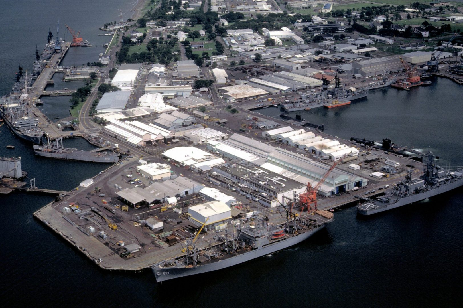 A view of the pier area with docked ships including the auxiliary stores ship USNS RIGEL (T-AF-58) and the nuclear-powered guided missile cruiser USS BAINBRIDGE (CGN-25) in the foreground. At left are the oiler USNS HASSAYAMPA (T-AO-145), the guided missile cruiser USS STERETT (CG-31), the guided missile destroyer USS HENRY B. WILSON (DDG-7) and the guided missile cruiser USS WILLIAM H. STANDLEY (CG-32).